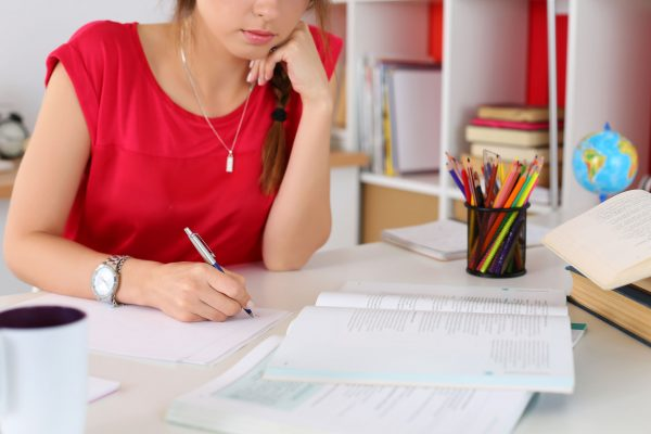 woman student sitting at desk at home studying