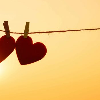 Two hearts pegged onto a line in the sunset