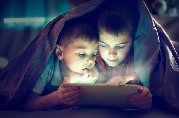 Children playing with a tablet at night under the covers