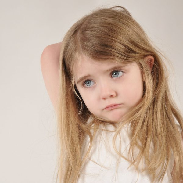 A little child looks sad and frustrated. The girl has her hand over her head for a parenting or tired concept.